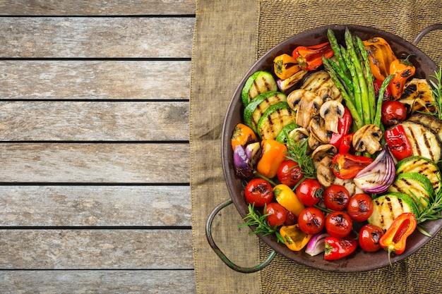 Concetto di cibo vegano, vegetariano, stagionale, estivo. verdure grigliate in padella su un tavolo di legno. vista dall'alto sullo sfondo dello spazio della copia piatta