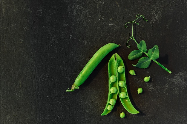 Sfondo vegetale con spazio copia per i tuoi progetti. chiuda in su dei piselli maturi freschi su priorità bassa nera