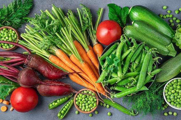 Sfondo di verdure. zucchine, carote, erbe aromatiche fresche su sfondo blu. vista dall'alto, primo piano.