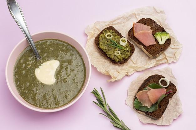 Zuppa di purea di broccoli vegetali in una ciotola bianca e panini