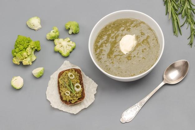 Zuppa di purea di broccoli vegetali in una ciotola bianca. cucchiaio vicino alla ciotola.