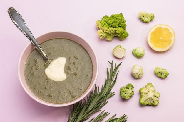 Zuppa di purea di broccoli vegetali in una ciotola bianca. cucchiaio nella ciotola. rametti di rosmarino, broccoli e limone.