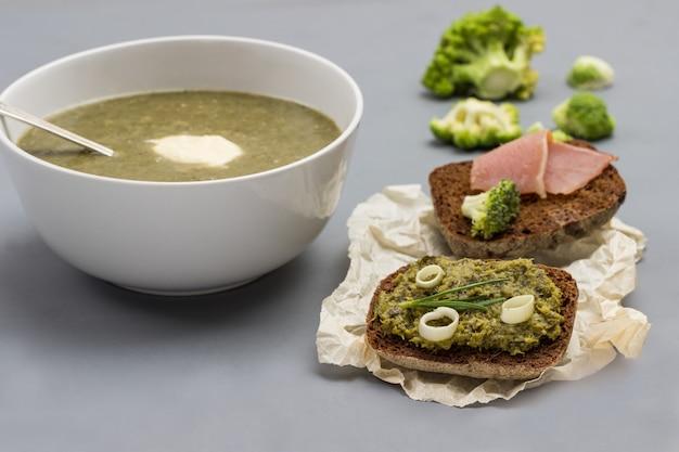 Zuppa di purea di broccoli vegetali in una ciotola bianca. cucchiaio nella ciotola. due bruschette su carta.