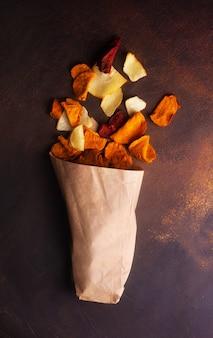 Chips di verdure a base di patate, carote e barbabietole sparse da un sacchetto kraft