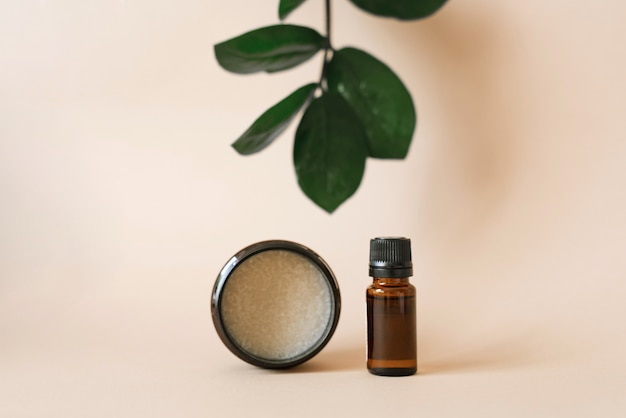 Cosmetici vegetali per la cura del corpo nei saloni di bellezza. bottiglia e vaso con oli su una parete beige con foglie di zamiokulkas verdi