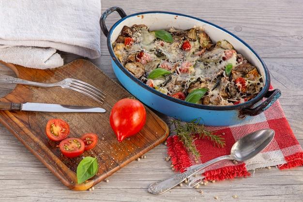 Verdure gratinate in un piatto su un tagliere