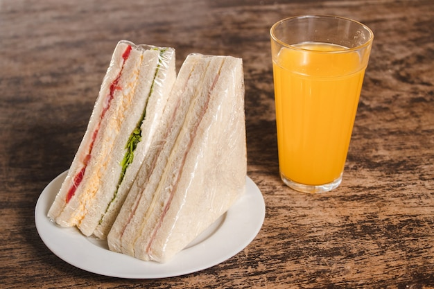 Panini di verdure e prosciutto e formaggio, con succo d'arancia su un tavolo di legno.