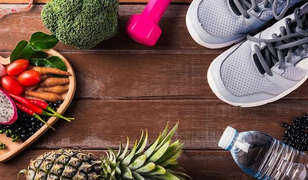 Verdura nel piatto cuore e scarpe sportive, manubri e acqua