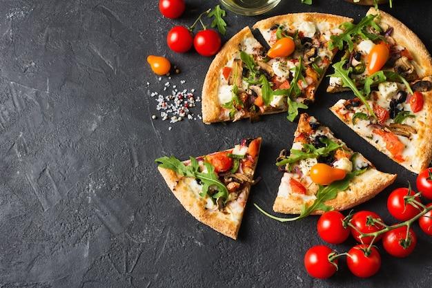 Pizza italiana di verdure con pomodori su sfondo nero, copia spazio, vista dall'alto
