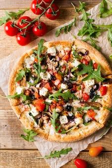 Pizza italiana di verdure con pomodori su sfondo wodeen, copia spazio, vista dall'alto, verticale