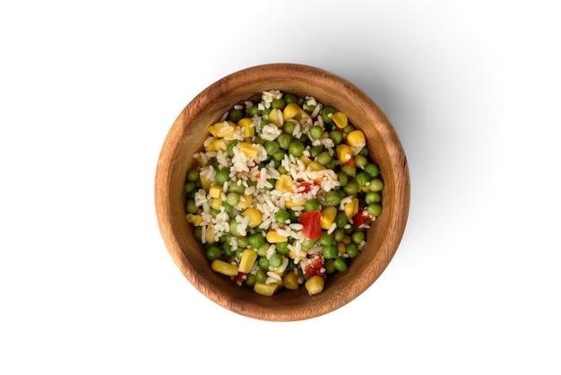 Mix di verdure messicano (hawaiano) di mais dolce, piselli, riso e pepe rosso in ciotola di legno isolata su sfondo bianco.