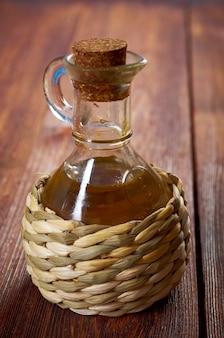 Primo piano della bottiglia di olio vegetale sul vecchio tavolo di legno