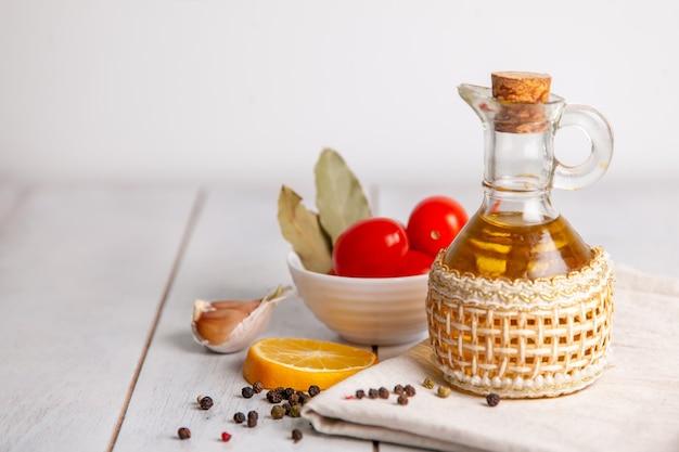 Olio vegetale in bottiglia su un asciugamano con pomodori, limone, pepe e alloro con copia spazio.