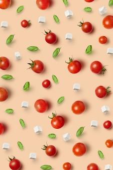Modello vegetale da ciliegia di pomodori sani maturi organici naturali appena raccolti, foglie di basilico e cubetti di formaggio