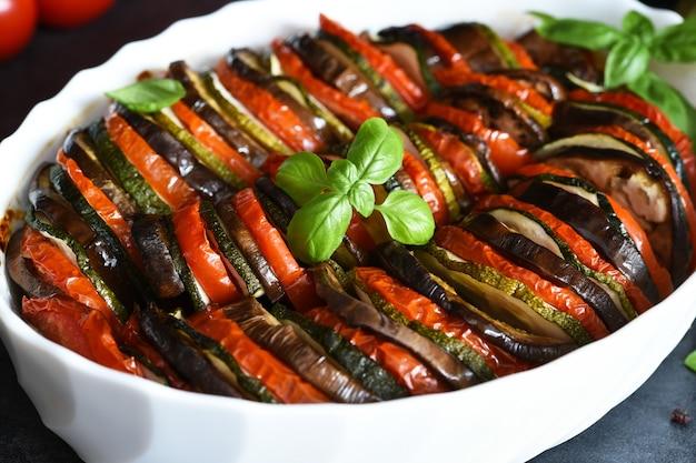 Ratatouille di verdure su fondo di cemento nero. verdure al forno sul tavolo della cucina.