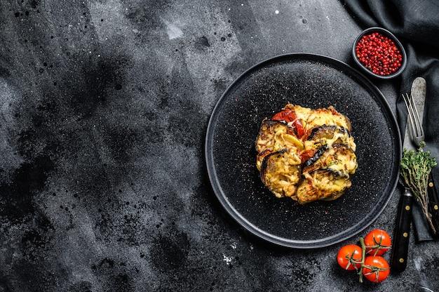 Ratatouille di verdure su un piatto. casseruola provenzale francese. sfondo nero. vista dall'alto. copia spazio.