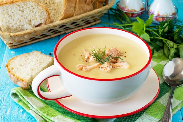 Zuppa di verdure e pesce rosso con panna e prezzemolo sullo sfondo di legno della cucina