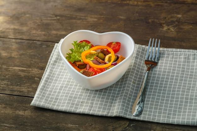 Insalata di verdure in un piatto a forma di cuore su un tavolo di legno su un tovagliolo a scacchi accanto a una forchetta.