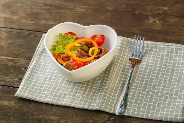 Insalata di verdure in un piatto a forma di cuore su un tavolo di legno su un tovagliolo.