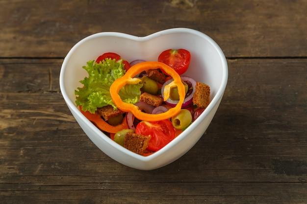 Insalata di verdure in un piatto a forma di cuore su un tavolo di legno.