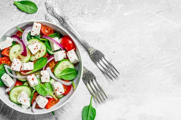 Insalata di verdure. insalata con verdure, formaggio e olio d'oliva sul tavolo rustico.