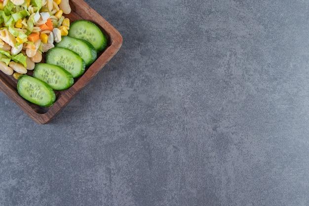 Insalata di verdure e cetrioli a fette su una tavola, sullo sfondo di marmo.