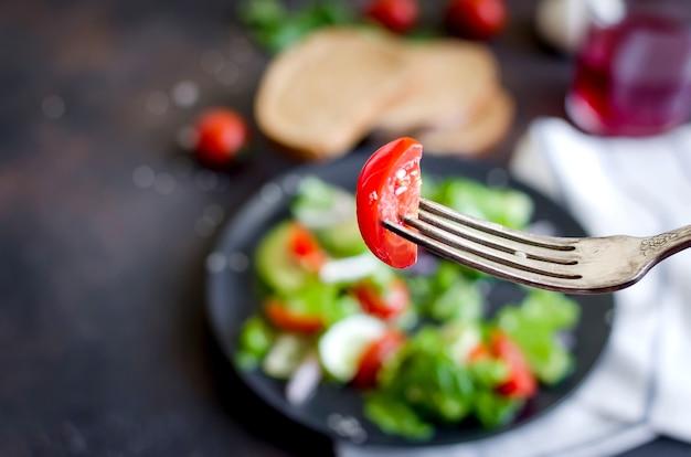 Insalata di verdure che abbiamo mangiato con pomodoro fresco, cetriolo, avocado, verdure e cipolle con sesamo per pranzo sul tavolo. concetto di cibo sano. copia spazio