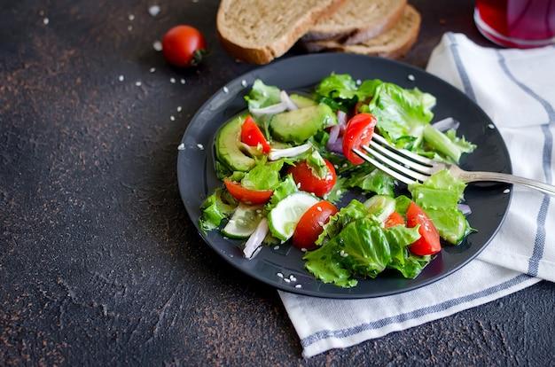 Insalata di verdure che mangiava con pomodoro fresco, cetriolo