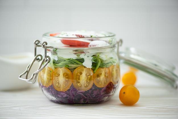 Insalata di verdure di pomodoro, cavolo e cetrioli in un barattolo