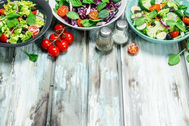 Insalata di verdure. una varietà di insalate biologiche, verdure con olio d'oliva e spezie sul tavolo rustico.