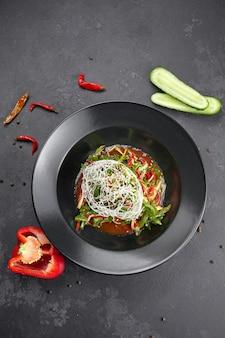 Insalata di verdure con rucola, peperone, cetriolo e semi di lino, su uno sfondo nero