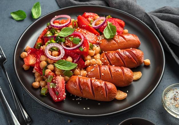 Insalata di verdure con ceci e semi di sesamo e salsicce in un piatto nero