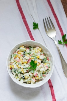 Insalata di verdure con bastoncini di granchio, condita con maionese. messa a fuoco selettiva.