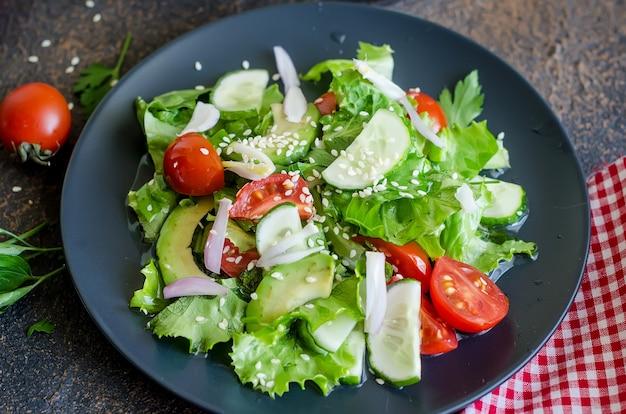 Insalata di verdure con pomodoro fresco, cetriolo, avocado, verdure e cipolle con sesamo per pranzo sul tavolo. concetto di cibo sano. copia spazio