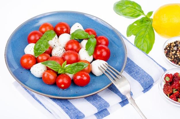 Insalata di verdure con palline di mozzarella sul piatto, sfondo bianco. foto dello studio.