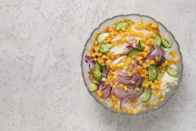 Insalata di verdure con cavolo alla pechinese, chicchi di mais dolce, cipolla affettata e cetriolo in una ciotola profonda su una superficie di cemento, vista dall'alto. concetto di cibo sano e vegano.