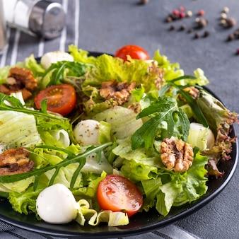 Insalata di verdure con pomodori, formaggio, rucola e noci.
