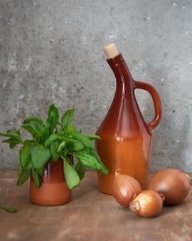 Set di verdure spinaci di cipolle in una pentola di terracotta e una bottiglia di argilla con olio vegetale su un une . marrone