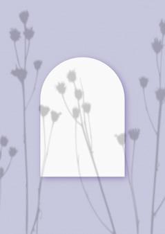 Ombre vegetali sovrapposte su un foglio a forma di arco di carta bianca testurizzata su uno sfondo di tavolo viola