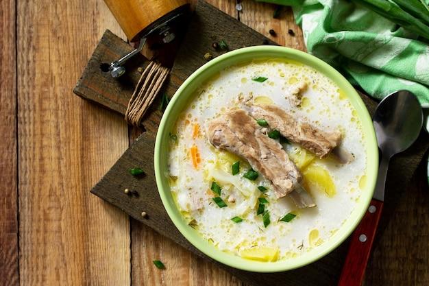 Zuppa di verdure con panna acida di cavolo e costolette di carne su un tavolo di legno da cucina vista dall'alto piatta