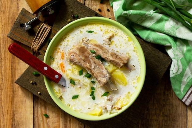 Zuppa di verdure con panna acida di cavolo e costolette di carne su un tavolo di legno da cucina vista dall'alto
