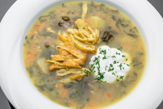 La minestra di verdura con la frittata arriva a fiumi una ciotola sulla tavola di legno rustica. zuppa dietetica con frittata, carota, piselli, porro, cavolfiore e patate.