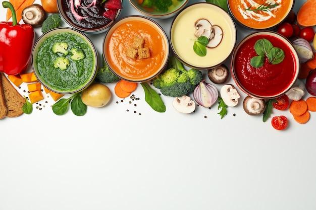 Minestre ed ingredienti di verdure su bianco, spazio per testo