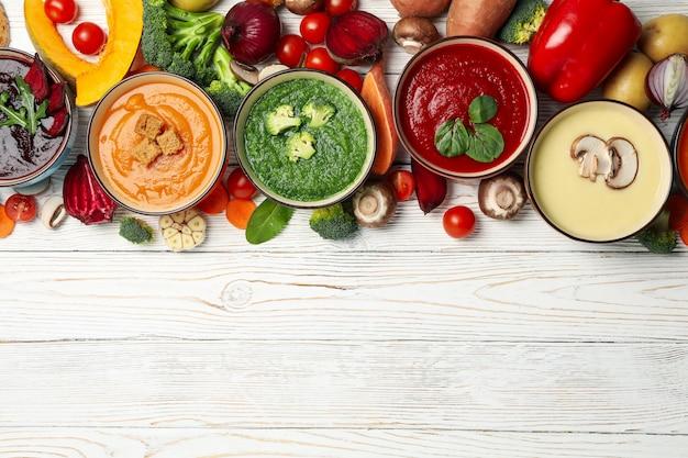 Minestre ed ingredienti di verdure sulla vista di legno e superiore bianca
