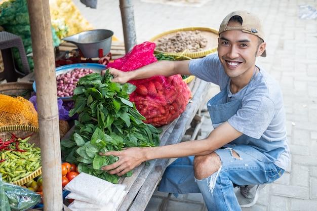 L'uomo di vendita di stallo di verdure sorride mentre tiene le verdure di spinaci sullo sfondo di una bancarella di verdure tradizionale