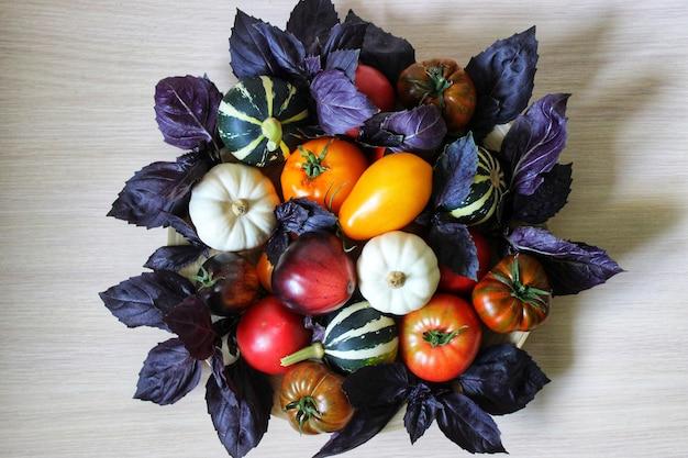Natura morta vegetale di piccole zucchine, pomodori e zucche