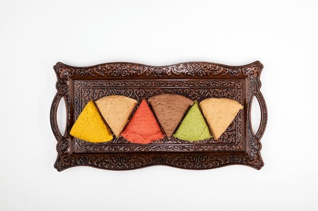 Halva a base vegetale con vari gusti su vassoio di metallo vista dall'alto di dolci orientali