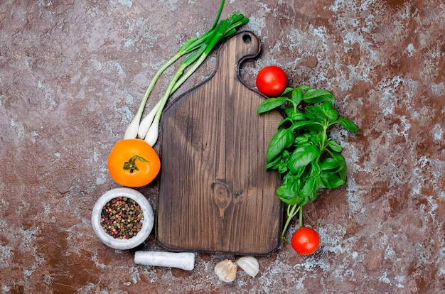 Verdure intorno a un tagliere di legno scuro, ingredienti per cucinare su uno sfondo di pietra scura. vista dall'alto, spazio di copia.