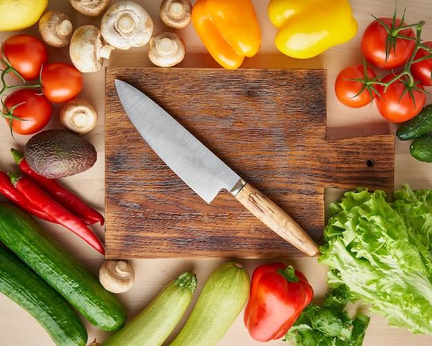 Verdure intorno al tagliere di legno con coltello sul tavolo della cucina. vista dall'alto.
