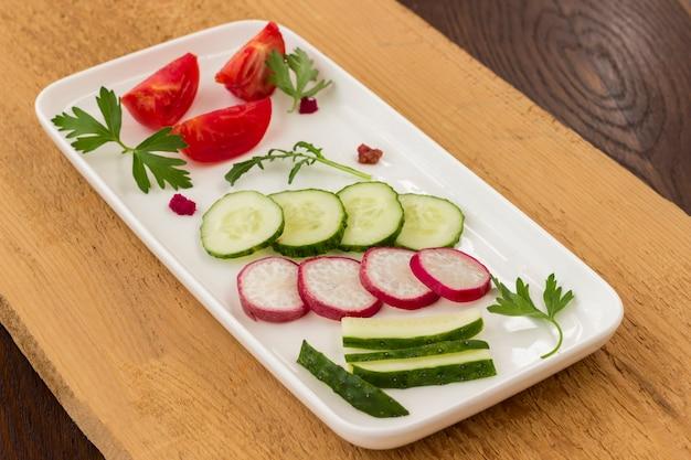 Verdure in un piatto di ceramica su una tavola rozza